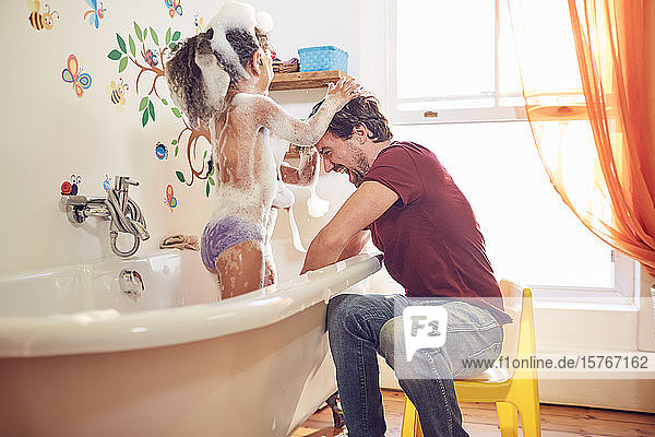 Playful father giving daughter bubble bath Playful father giving daughter bubble bath