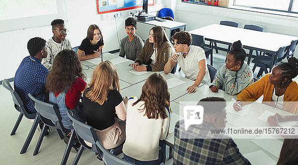 Highschool-Schüler unterhalten sich im Debattierkurs am Tisch