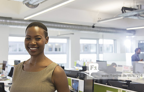 Portrait smiling  confident businesswoman in open plan office