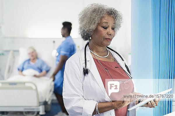 Female senior doctor using digital tablet in hospital room Female senior doctor using digital tablet in hospital room