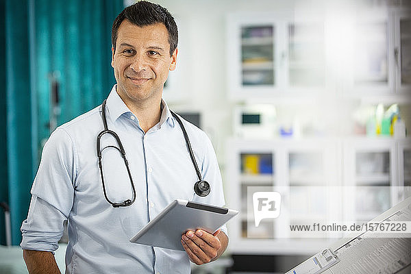Portrait confident male doctor with digital tablet in hospital