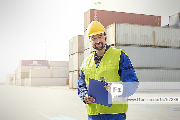 Portrait confident dock worker with clipboard at shipyard