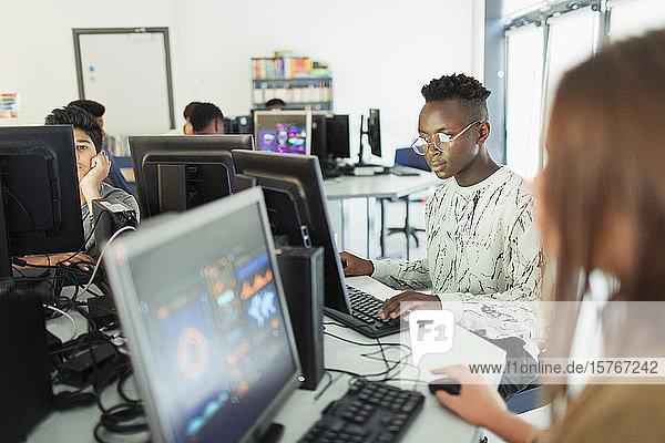 Focused junior high boy student using computer in computer lab Focused junior high boy student using computer in computer lab