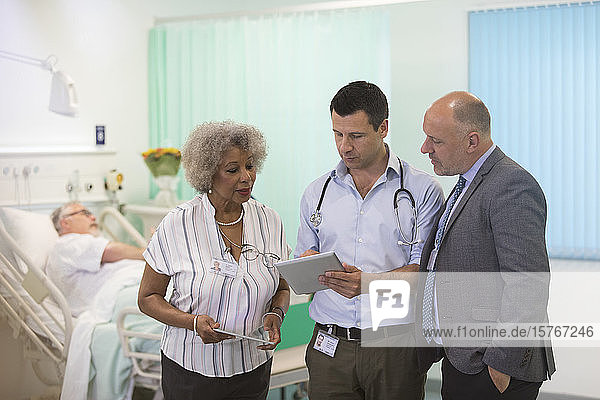 Doctors with digital tablets making rounds  consulting in hospital room