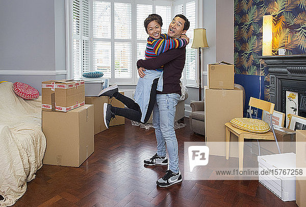 Portrait happy  playful couple moving into new house