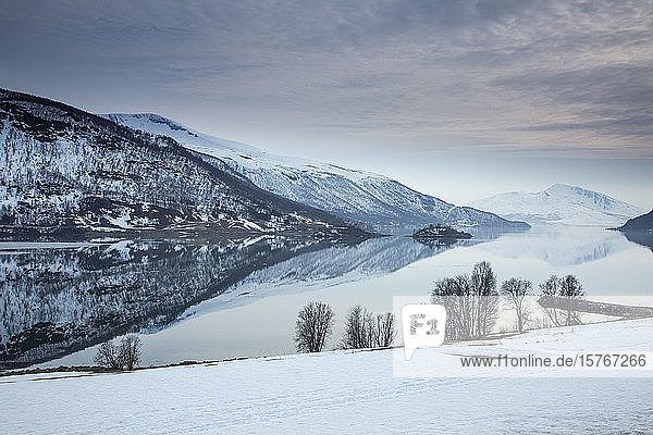 Tranquil lake and snow covered mountains Norway