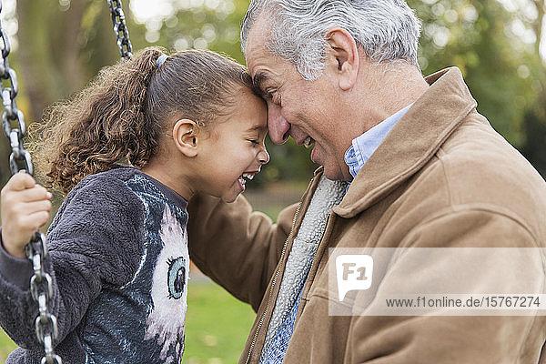 Verspielter  liebevoller Großvater und Enkelin auf einer Schaukel auf dem Spielplatz