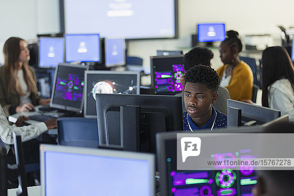 Focused junior high boy student using computer in dark computer lab