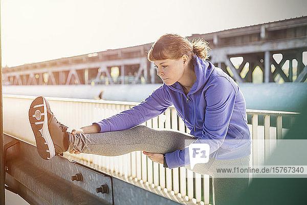 Young female runner stretching leg on urban railing