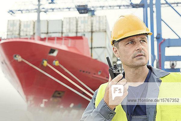 Dock worker using walkie-talkie below container ship at shipyard