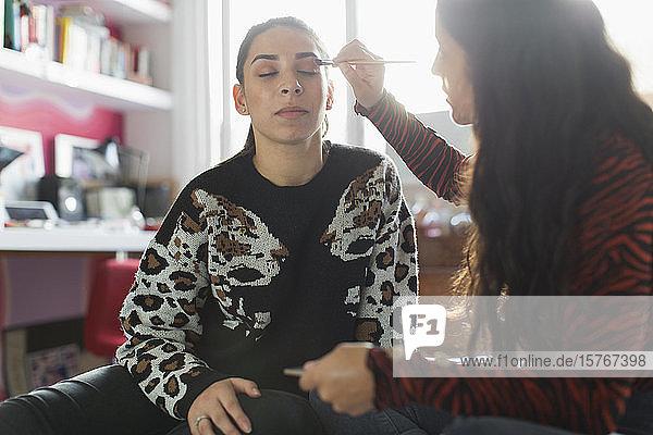 Teenage girl applying eyeshadow makeup to friends eyes