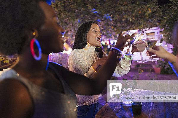 Glückliche junge Frauen trinken Cocktails auf einer Hinterhofparty