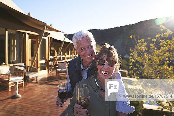 Porträt glückliches älteres Paar trinkt Eistee auf sonnigem Hotelbalkon