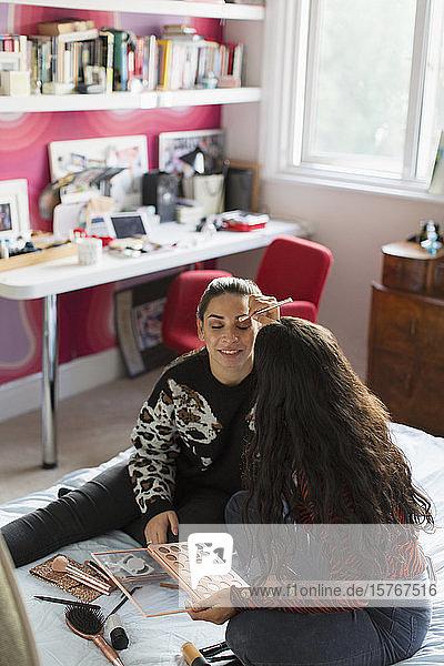 Teenage girl applying eyeshadow makeup to friends eyes on bed
