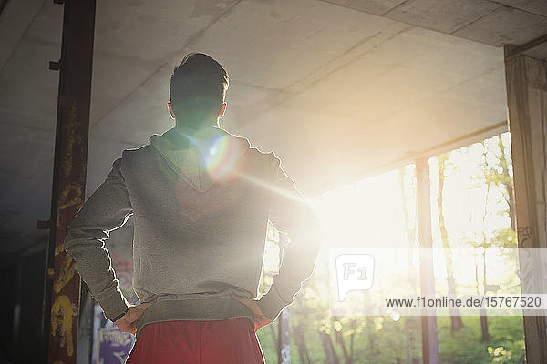 Young male runner resting  standing with hands on hips in sunny abandoned building