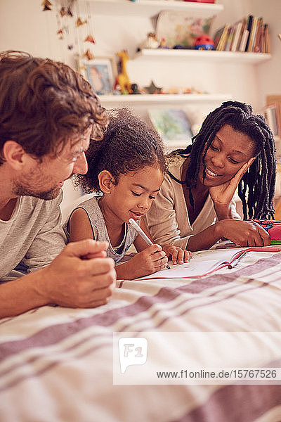 Young family coloring on bed Young family coloring on bed