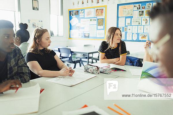 Gymnasiasten im Gespräch und beim Lernen am Tisch im Klassenzimmer