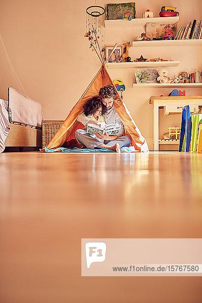 Vater und Tochter lesen ein Buch im Tipi