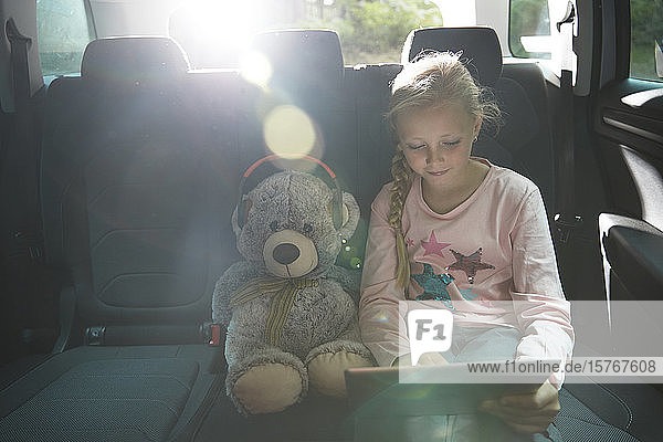 Girl with teddy bear using digital tablet in back seat of car
