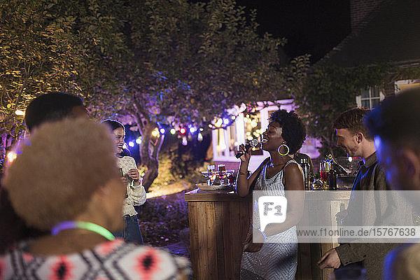 Junge Frau mit Mikrofon singt auf einer Gartenparty