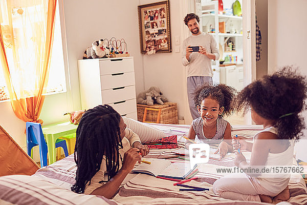 Young family coloring on bed