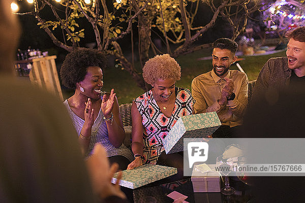 Friends watching woman open birthday gift at garden party