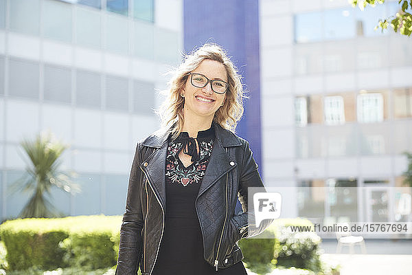 Portrait confident woman in leather jacket outside sunny building