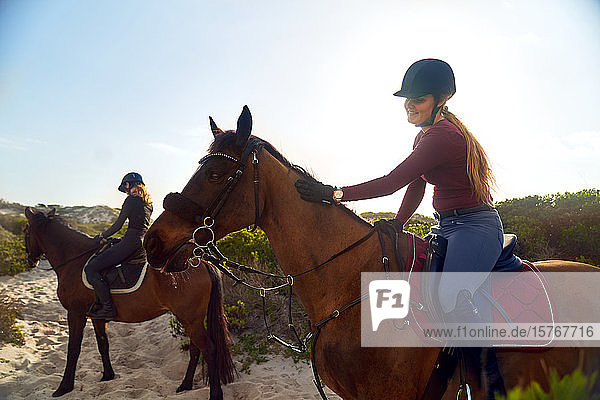 Young women horseback riding on beach