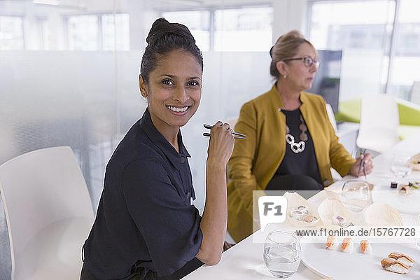 Porträt einer lächelnden  selbstbewussten Geschäftsfrau beim Sushi-Mittagessen