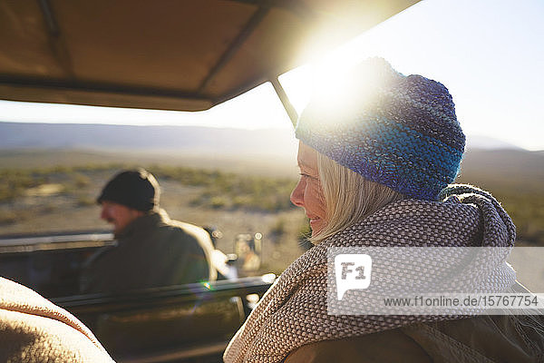 Happy senior woman riding in sunny safari off-road vehicle Happy senior woman riding in sunny safari off-road vehicle