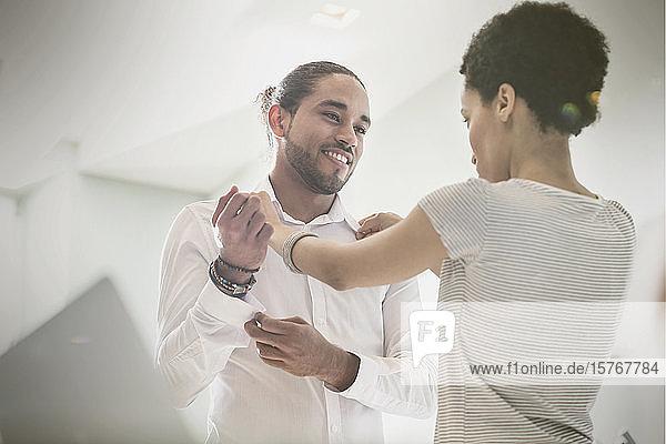 Woman helping boyfriend getting dressed  adjusting shirt collar