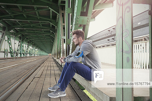 Young male runner resting on urban train station platform