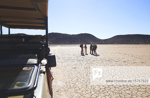 Safari tour group walking in sunny arid desert South Africa