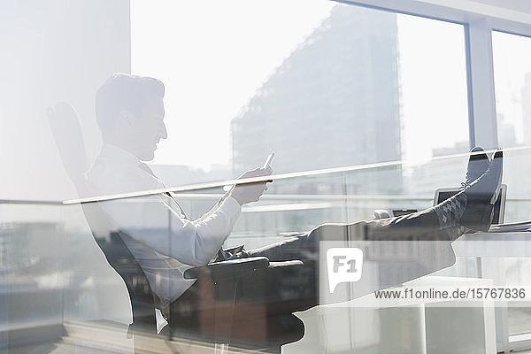 Geschäftsmann mit Smartphone in einem sonnigen  städtischen Büro