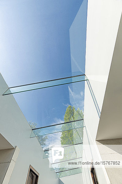 Modern glass skylight below sunny blue sky