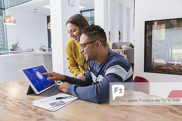 Ehepaar bezahlt Rechnungen auf digitalem Tablet