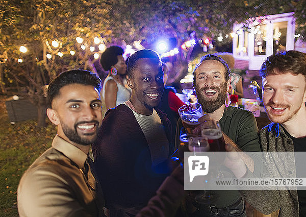 Portrait happy male friends drinking at garden party Portrait happy male friends drinking at garden party