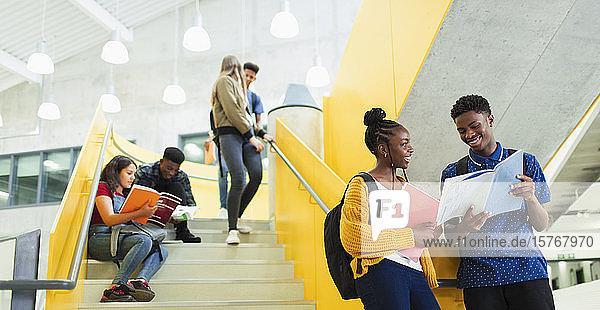 Schüler der Mittelstufe unterhalten sich und lernen auf einer Treppe