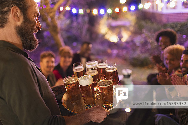 Man serving tray of beers to friends at garden party