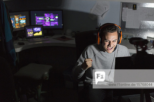 Excited teenage boy with headset cheering  playing video game in dark room