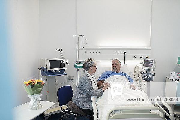 Senior woman visiting  comforting husband resting in hospital bed
