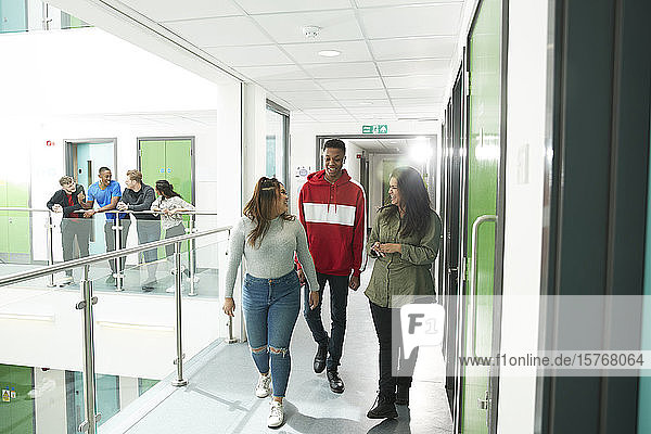 College students walking and talking in corridor