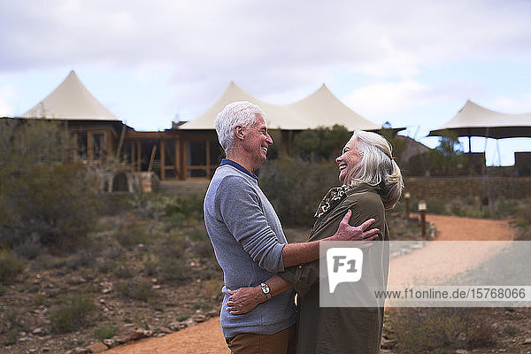 Affectionate senior couple hugging outside safari lodge hotel
