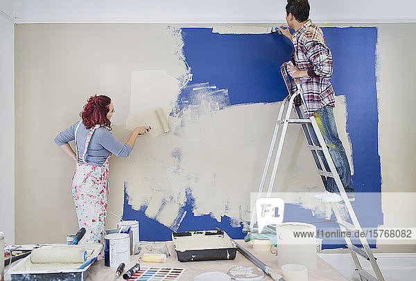 Couple redecorating  painting wall