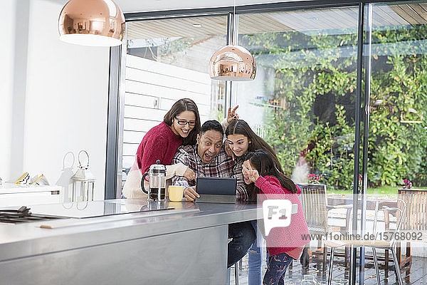 Playful family taking selfie with digital tablet in morning kitchen