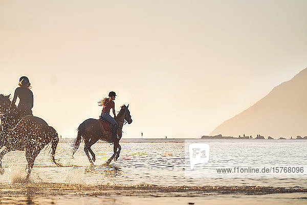 Young women horseback riding in ocean surf at sunset