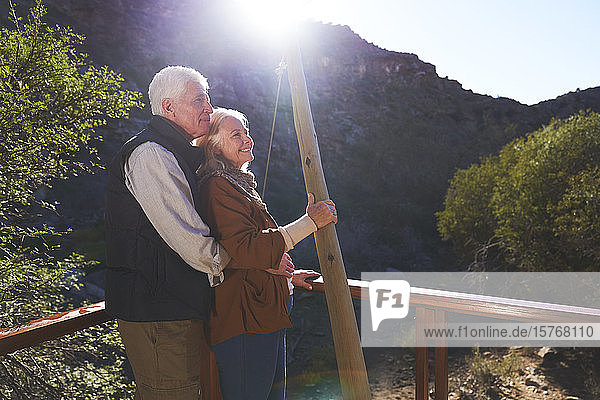 Glückliches älteres Paar entspannt auf sonnigem Balkon