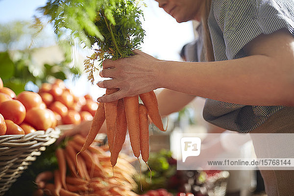 Woman holding bunch of carrots at farmer's market Woman holding bunch of carrots at farmer's market