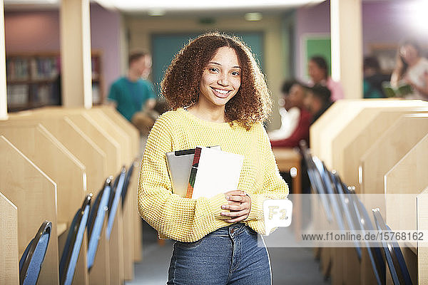Portrait confident smiling young female college student in library