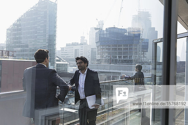 Businessmen talking on sunny  urban highrise office balcony